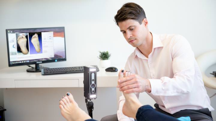 Podiatry practitioner examines a patient